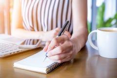 Hand för affärskvinna som arbetar på en dator och skriver på en notep Fotografering för Bildbyråer