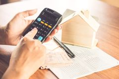 Hand för affärskvinna som räknar pappers- valuta för pengar med besparingkontoboken, husmodellen och räknemaskinen på skrivbordet Royaltyfri Foto