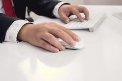 Hand för affärsman genom att använda datormusen Arkivbild