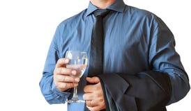 Hand för affärsman som rymmer exponeringsglas av vatten för beröm Vit bakgrund royaltyfri foto