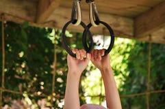 Hand för barn` som s är hållande på till en metallcirkel i lekplatsen fotografering för bildbyråer