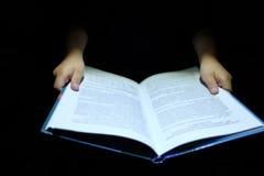 Hand för barn` som s rymmer en bok Arkivbild