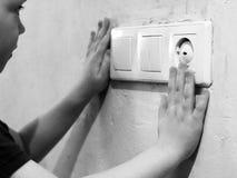 Hand för barn` som s symboliserar fara av en elektrisk ström arkivfoton