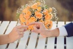 Hand för brudgum` som s anfaller Brode ` s ett arkivfoto