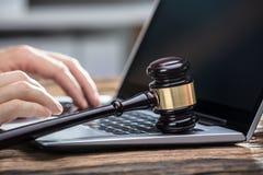 Hand för Businessperson` s genom att använda bärbara datorn på träskrivbordet royaltyfria foton