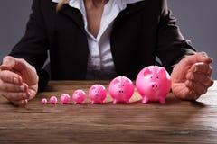 Hand för Businessperson` som s skyddar Piggybanks royaltyfri foto