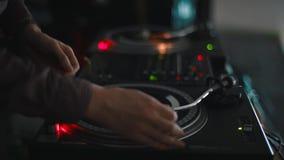 Hand för discjockey` som s spelar musik på skivtallriken på ett parti stock video