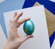 hand för easter äggkvinnlig På en geometrisk bakgrund blåa färger royaltyfri bild