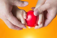 Hand för faderhållunge på orange bakgrund Arkivfoton