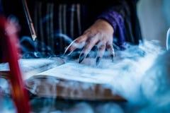 Hand för häxa` s på den magiska boken Arkivfoton