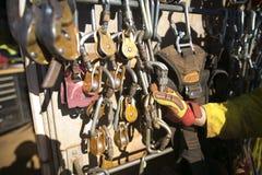 Hand för inspektör för tekniker för reptillträdesgruvarbetare som kontrollerar säkerhetskontrollen på descenders som låser carabi arkivfoton