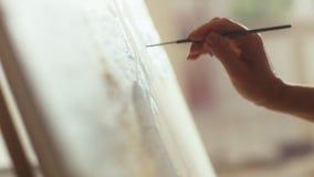 Hand för konstnärkvinna` s med borstemålningbilden på kanfas i dagsljuskonststudio lager videofilmer