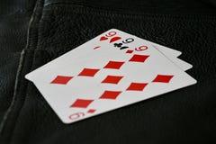 Hand för 999 kort på svart texturerad bakgrund arkivfoton