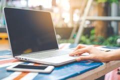 Hand för kvinna` s genom att använda en tom skärm för anteckningsbokdator på ett trä Royaltyfri Foto