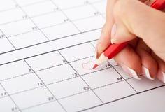 Hand för kvinna` s med blyertspennan och kalendern Arkivfoto