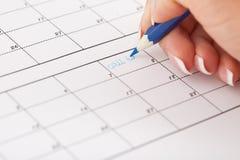 Hand för kvinna` s med blyertspennan och kalendern Royaltyfria Bilder