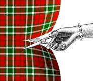 Hand för kvinna` s med sax som klipper tartantyg Royaltyfri Bild