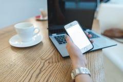 Hand för kvinna` s med telefonen i hand mot bärbar dator- och kaffebakgrund äganderätt för home tangent för affärsidé som guld- n Arkivfoton