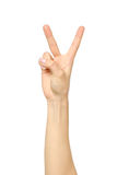 Hand för kvinna` s med två fingrar upp i fred- eller segersymbolet arkivfoto