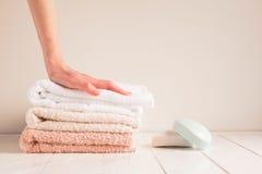 Hand för kvinna` s och en bunt av mjuka handdukar med tvål på en lantlig tabell Begreppet av en sund handhud royaltyfria foton