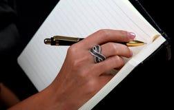 Hand för kvinna`s skriva-på anteckningsboken Royaltyfri Foto