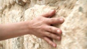 Hand för kvinna` som s flyttar sig över den gamla stenväggen Glidning along Sinnligt trycka på Hård stenyttersida