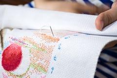 Hand för kvinna` som s gör kors-att sy med visaren royaltyfri foto