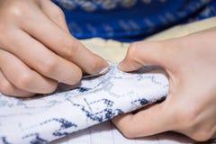 Hand för kvinna` som s gör kors-att sy med visaren royaltyfria bilder