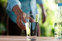 Hand för kvinna` som s når för exponeringsglaset av dricksvatten arkivfoton