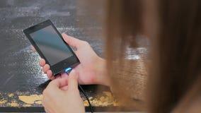 Hand för kvinna` som s pluggar laddande kabel för svart blixt in i smartphonen arkivfilmer