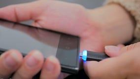 Hand för kvinna` som s pluggar laddande kabel för svart blixt in i smartphonen Royaltyfri Fotografi