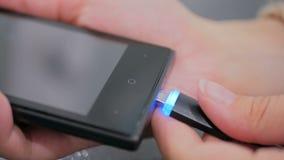 Hand för kvinna` som s pluggar laddande kabel för svart blixt in i smartphonen Arkivfoto