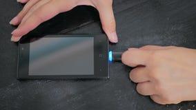 Hand för kvinna` som s pluggar laddande kabel för svart blixt in i smartphonen Fotografering för Bildbyråer