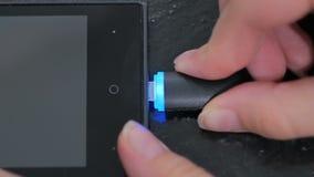 Hand för kvinna` som s pluggar laddande kabel för svart blixt in i smartphonen Royaltyfria Bilder