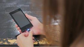 Hand för kvinna` som s pluggar laddande kabel för svart blixt in i smartphonen Royaltyfria Foton