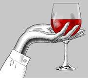 Hand för kvinna` som s rymmer ett exponeringsglas med rött vin Royaltyfria Bilder