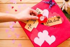 Hand för kvinna` som s sätter en origamihjärta till asken för gåva för dag för valentin` s den röda med ett mellanrum för pappers Royaltyfria Foton