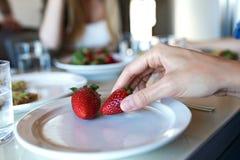 Hand för kvinna` som s tar jordgubbar av en platta i köket royaltyfri foto