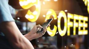 Hand för man` s genom att använda den mobila smartphonen i kafé fotografering för bildbyråer