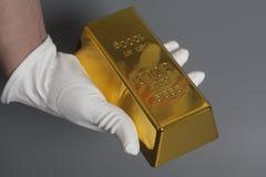 Hand för man` s i vita handskar som rymmer en guld- guldtacka Royaltyfri Foto