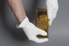 Hand för man` s i vita handskar som rymmer en guld- guldtacka Arkivbild