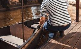 Hand för man s med det tiying repet för fartyg Sjömansjömangondoljären Yachtsman förtöjer hans motorfartyg på bryggan Stäng sig u arkivfoto
