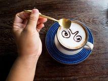 Hand för man` som s rymmer en kaffesked med kaffekoppen Arkivfoto