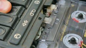 Hand för man` som s sätter in ljudkassetten in i den gamla smutsiga retro bandspelaren stock video