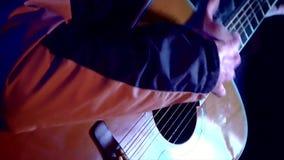 Hand för man` som s spelar en gitarr med ett armband på Gitarren tänds av ljuset från en lägereld, som folket sjunger lägereldsån stock video