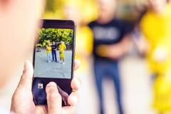 Hand för man` som s tar en bild av vänner på mobiltelefonen arkivfoton