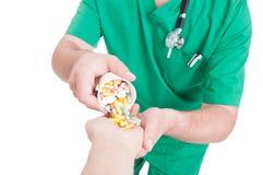 Hand för preventivpillerar för doktor, för läkare eller för apotekare hällande tålmodig in - Arkivfoton