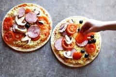 Hand för ` s för tonårs- flicka som sätter skivan av tomaten på rå pizza Royaltyfria Bilder