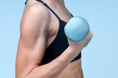 Hand för sportkonditionflickor med hanteln på en grå bakgrund royaltyfri fotografi