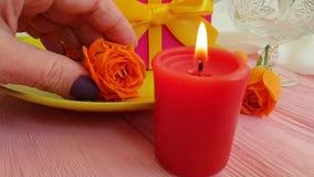 Hand för ultrarapid för platta för brand för stearinljus för blomma för ros för gåvaask arkivfilmer